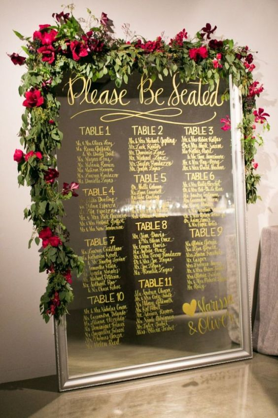 an oversized mirror seating chart with a lush greenery and red bloom garland