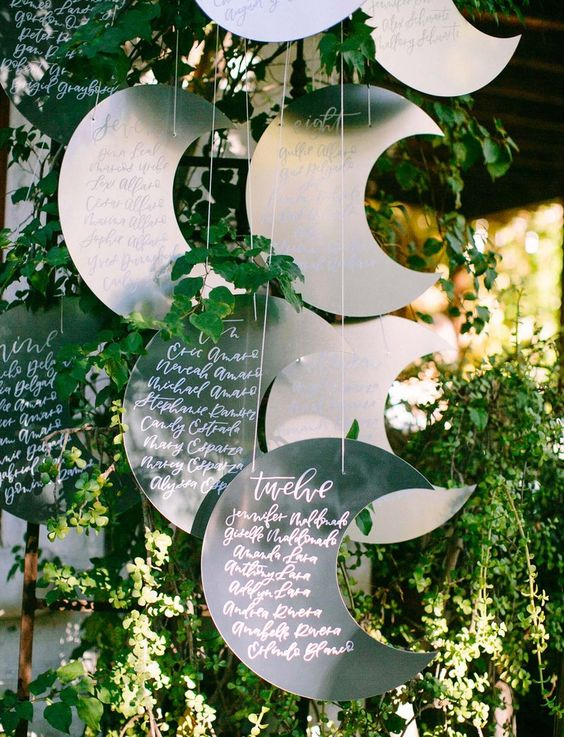 metal crescent moon seating chart in the greenery is a cute idea to rock