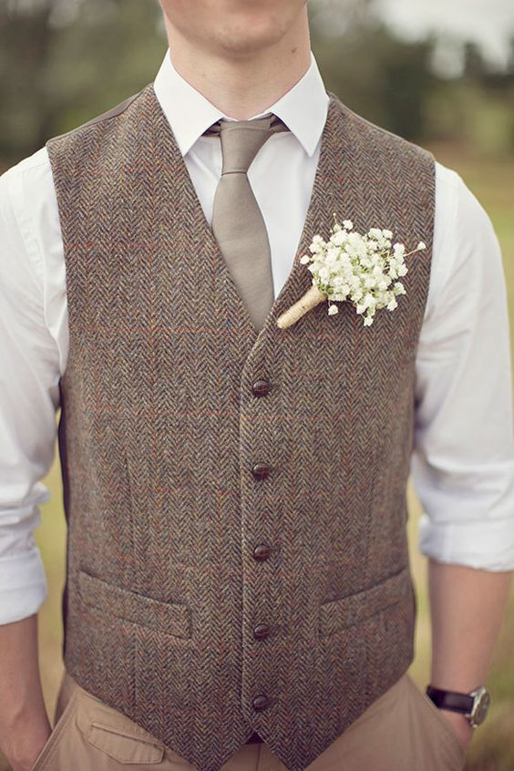 tan pants, a white shirt, a grey tie, a brown tweed vest and a baby's breath boutonniere