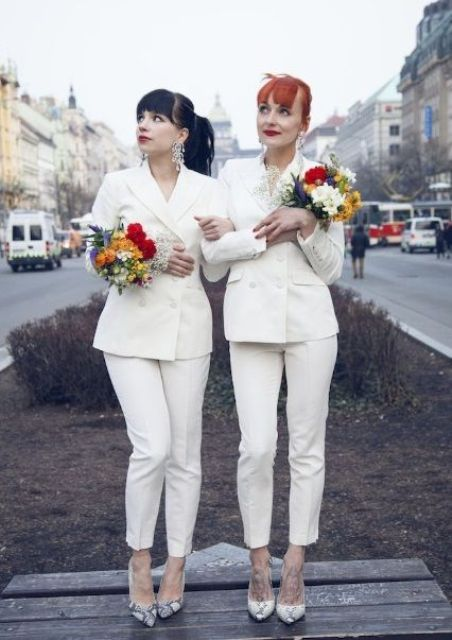 two bride wearing same pantsuits with cropped pants, statement earrings and snake print shoes