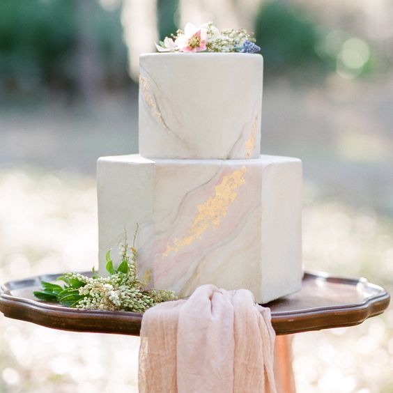 a subtle pastel marbleised wedding cake of a geometric shape with gold leaf and blooms on top