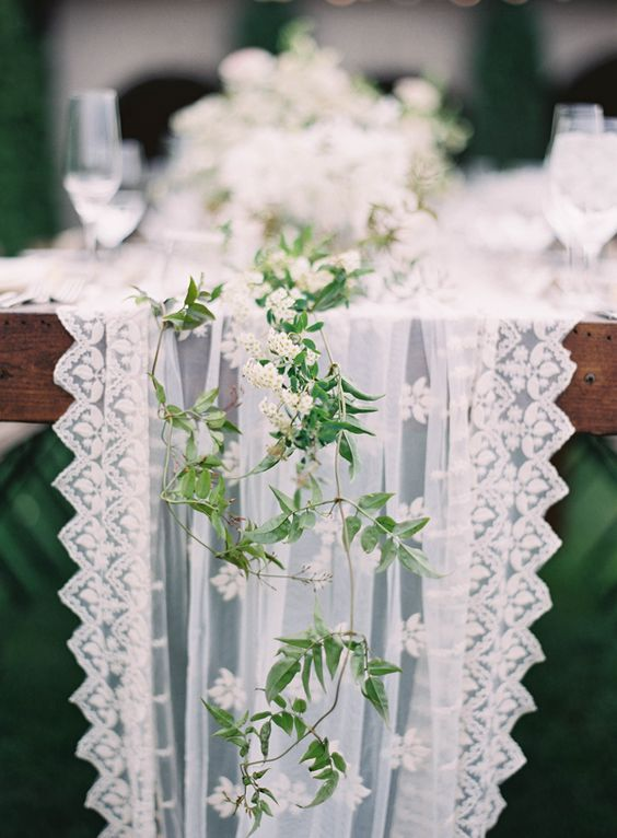 a gorgeous tulle and lace table runner with fresh greenery and white flowers in one for an airy look