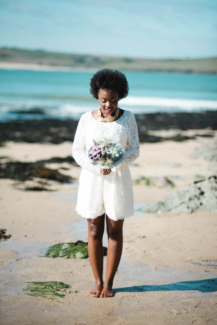 The bride was wearing a lace romper with long sleeves and a statement necklace