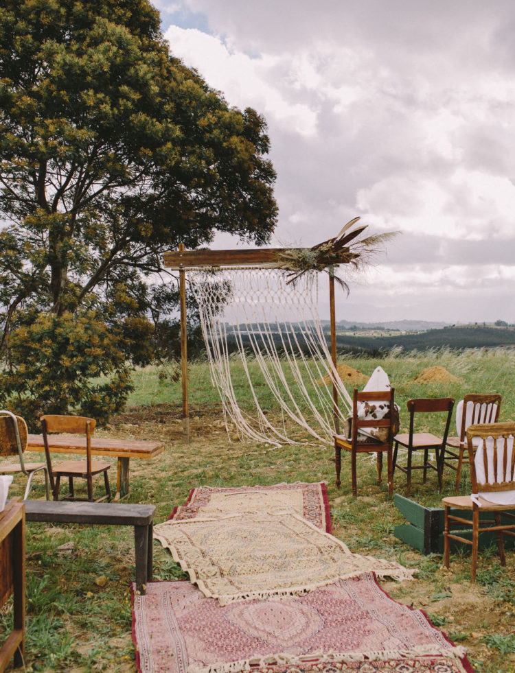 The wedding ceremony space was done with various rugs, mismatching chairs and an arch with macrame, pampas grass and feathers