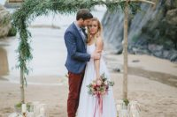 02 a boho beach wedding arch with greenery and some candle holders around