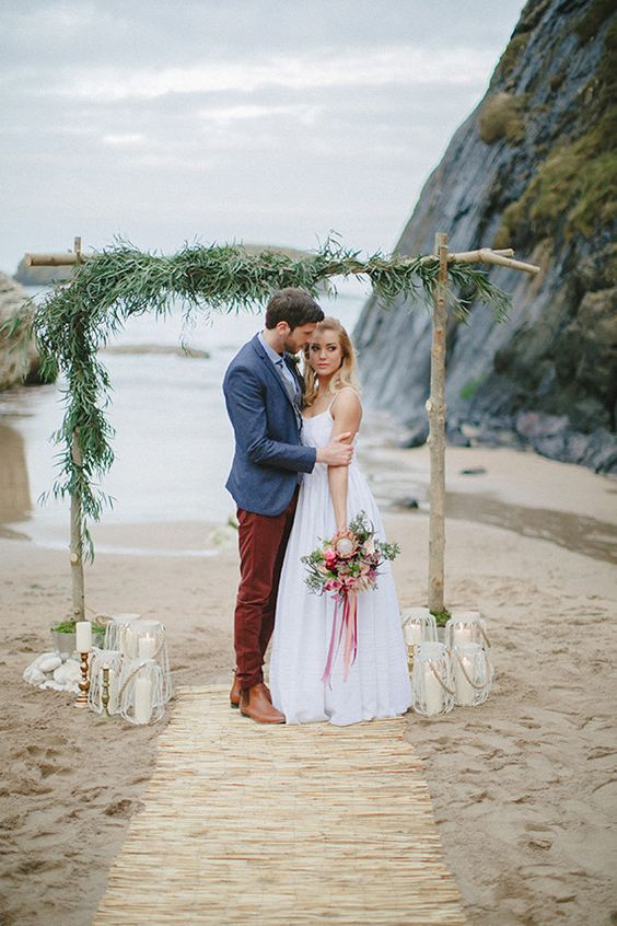 a boho beach wedding arch with greenery and some candle holders around