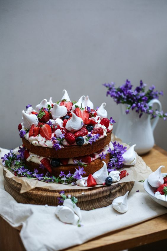 a bold naked sponge cake with strawberries, raspberries, meringues and purple flowers for a mid-summer wedding