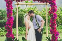 02 a colorful tropical wedding arch with fuchsia and hot pink blooms and monstera leaves