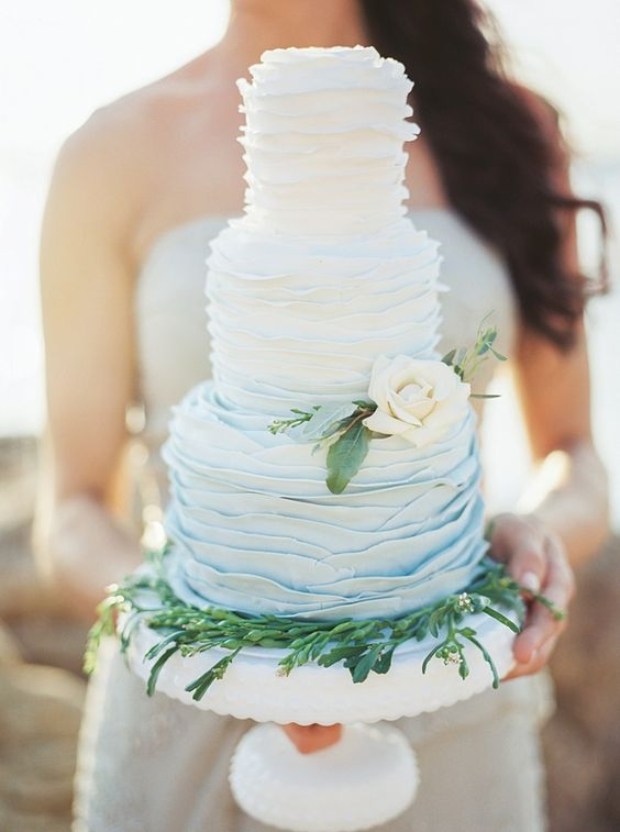 a ruffled ombre wedding cake from white to blue, with greenery and a neutral flower