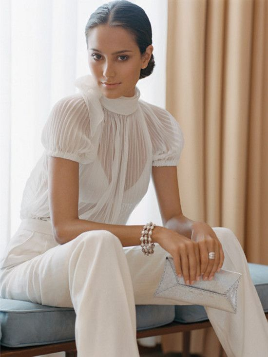 a white jumpsuit with a sheer pleated bodice and short sleeves and plain pants for a modern bride