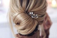 02 an elegant and effortlessly chic chignon with some locks down and messy volume on top plus a rhinestone hairpiece