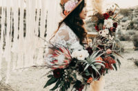 03 She was also rocking a hat decorated with blooms and cacti and her lush bouquet was done with proteas, air plants and red and burgundy blooms