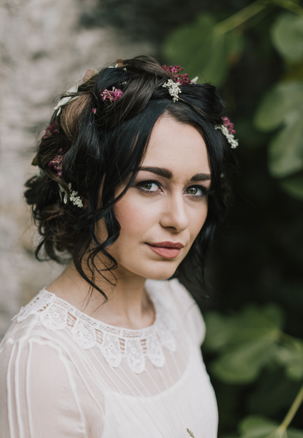 She was rocking a loose halo braid with flowers and leaves scattered between for a rustic chic and boho feel