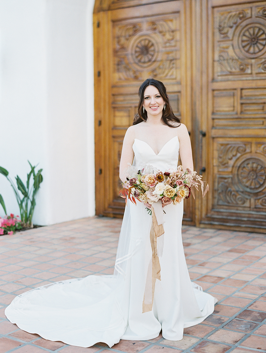 The bride was wearing a gorgeous wedding gown with an illusion neckline, a long train and a row of buttons on the back