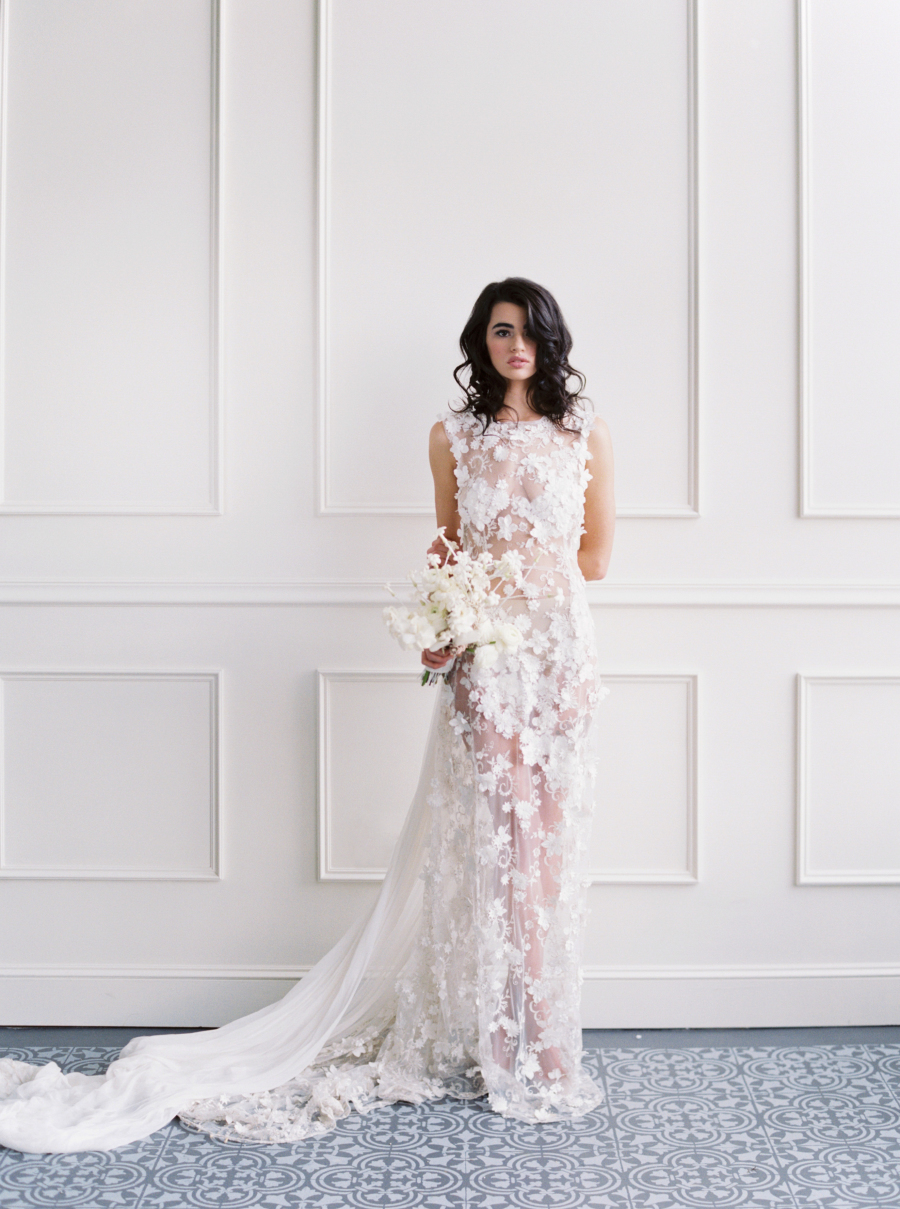 The bride was wearing a stunning sheer wedding dress with no sleeves, fully covered with white floral appliques