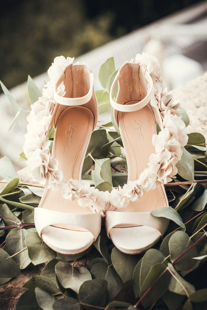 The bride was wearing neutral wedding shoes with ankle straps and with florals