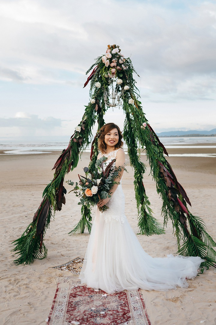 The wedding arch was teepee-like, with luch greenery, dark leaves and a glam chandelier for a shiny touch