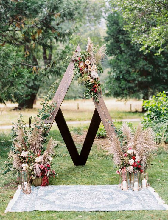 a boho wooden arch decorated with greenery, fall colored blooms and pampas grass plus candles in geometric candle holders