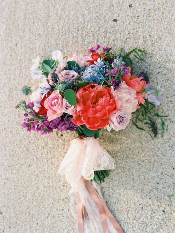 a cool colorful wedding bouquet in red, mauve, pink, blue and purple plus lace and blush ribbons hanging down