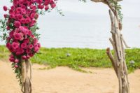 03 a driftwood wedding arch with greenery and ombre pink flowers on one corner