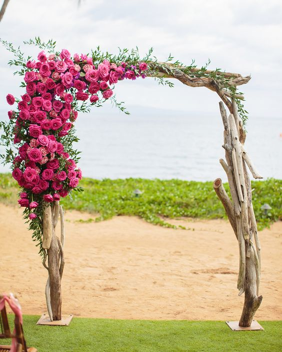 a driftwood wedding arch with greenery and ombre pink flowers on one corner