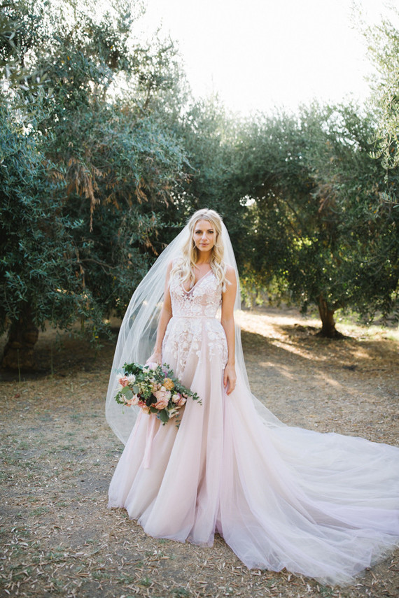 Her gorgeous wedding dress was a lush one with white lace floral appliques and a deep V-neckline