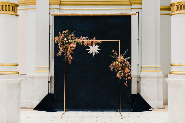 The amazing wedding arch was done of gold piping, a star and large moody asymmetrical florals
