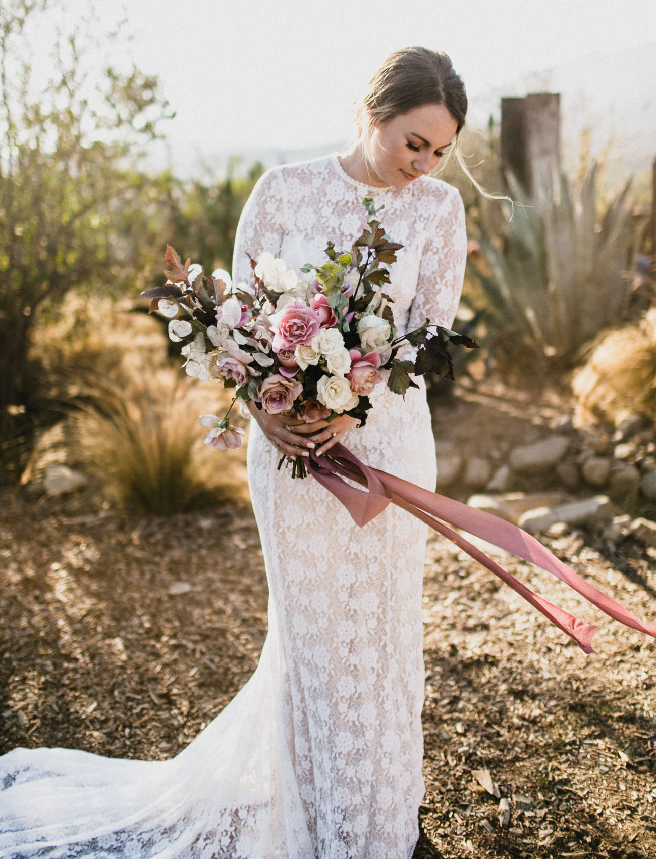 The bride was wearing a lace sheath wedding dress with long sleeves, a train and an illusion neckline