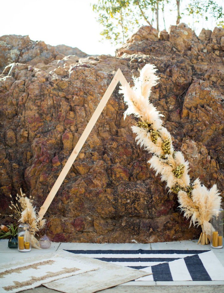 The wedding arch was triangle, with greenery, candles and pampas grass