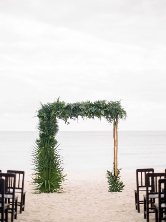 a branch wedding arch decorated with lush tropical leaves for a tropical beach wedding