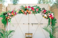 04 a colorful tropical wedding arch with palm leaves, orange, red, fuchsia and yellow blooms