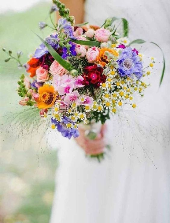 a colorful wildflower wedding bouquet in purple, yellow, pink, fuchsia and with greenery and herbs