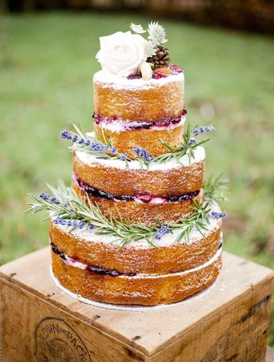 a country chic naked wedding cake with berries, lavender and a pinecone and a white rose on top