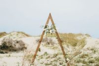 04 a desert ceremony arch with a floral posie hanging inside and some branches and candles at the base