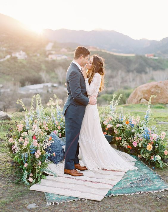 a gorgeous boho wedding altar of pink, peachy and blue blooms with greenery looks very textural