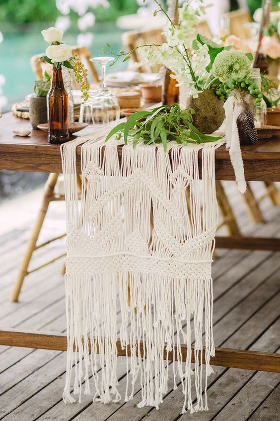 a macrame table runner is great for a boho wedding, add greenery or blooms on top