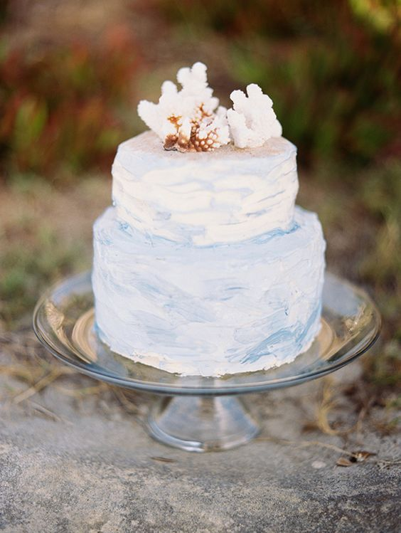 an ombre blue watercolor wedding cake with corals on top is ideal for a beach wedding