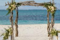 05 a branches wedding arch with greenery and neutral blooms and a gorgeous sea backdrop