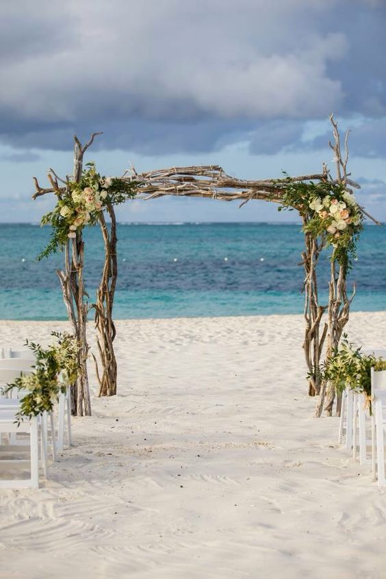 a branches wedding arch with greenery and neutral blooms and a gorgeous sea backdrop