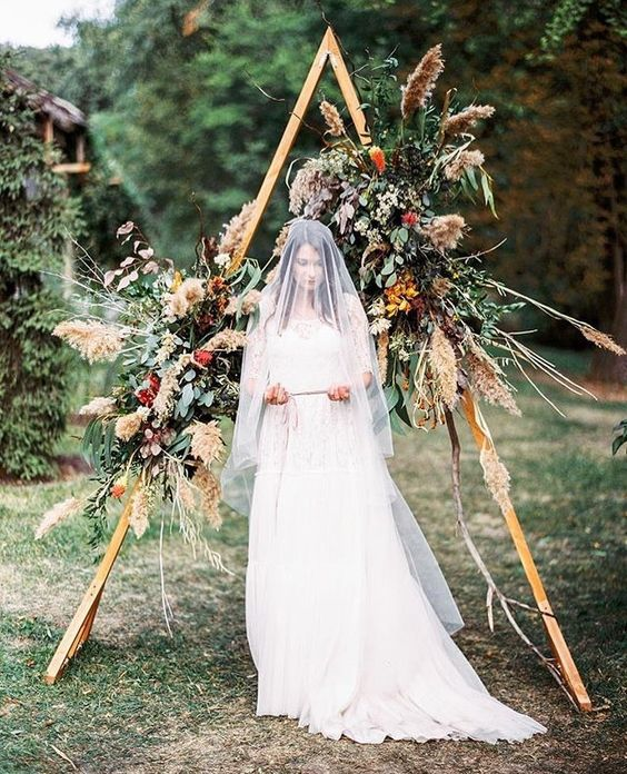 a gorgeous fall boho wedding arch with pampas grass, leaves, herbs and fall leaves for a textural look