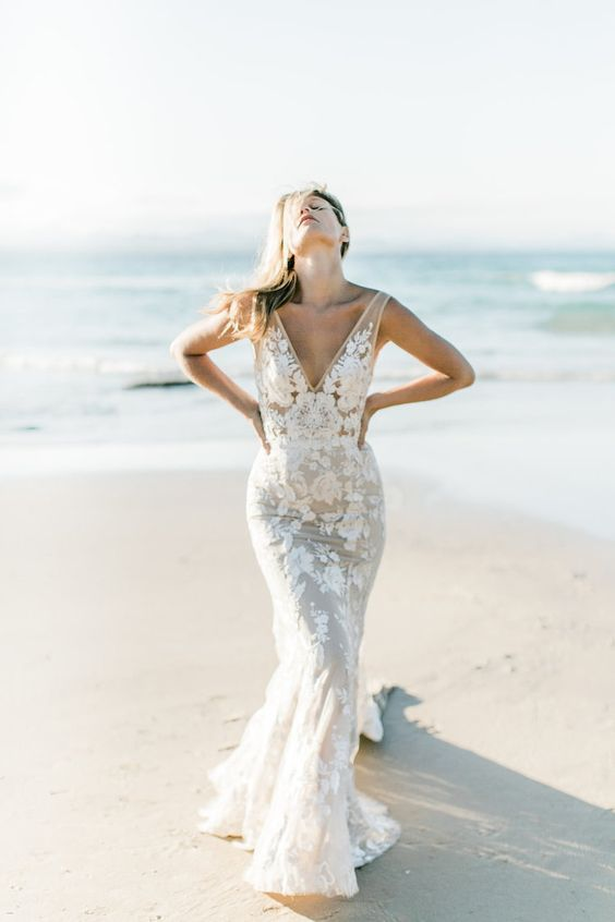 a gorgeous sheath wedding dress with thick straps, a deep V-neckline and lace appliques for a glam statement