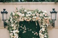05 a greenery wall framed with very lush ivory and blush flowers looks very cute and romantic