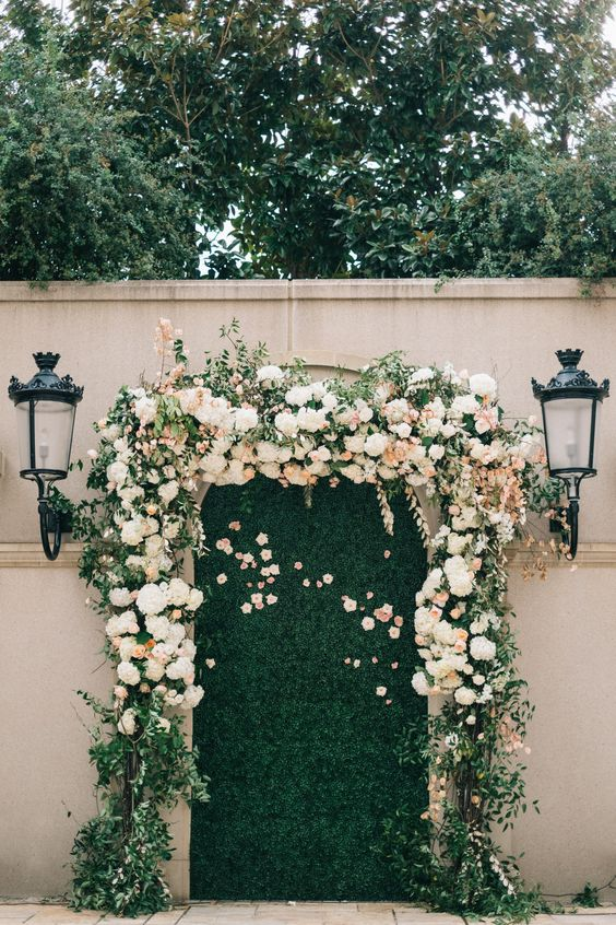 a greenery wall framed with very lush ivory and blush flowers looks very cute and romantic