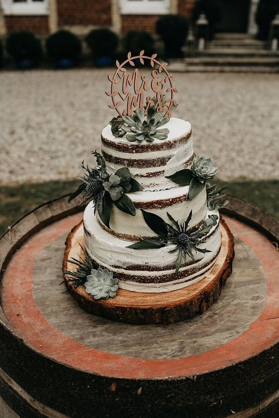 a naked buttercream sponge wedding cake with thistles and succulents plus a calligraphy topper