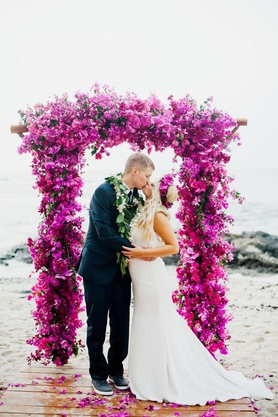 a super lush and bold wedidng arch of fuschia orchids and bouganvilla