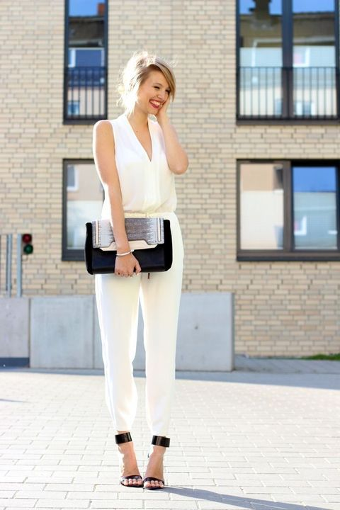 a white sleeveless fitting jumpsuit with a V neckline, black ankle strap shoes and a matching clutch for a modern bride