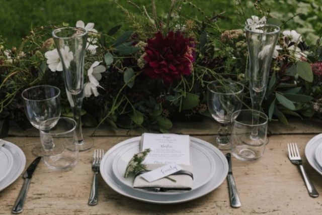 The wedding tablescape was done with lush greenery and some blooms, clear glasses, neutral flatware and plates