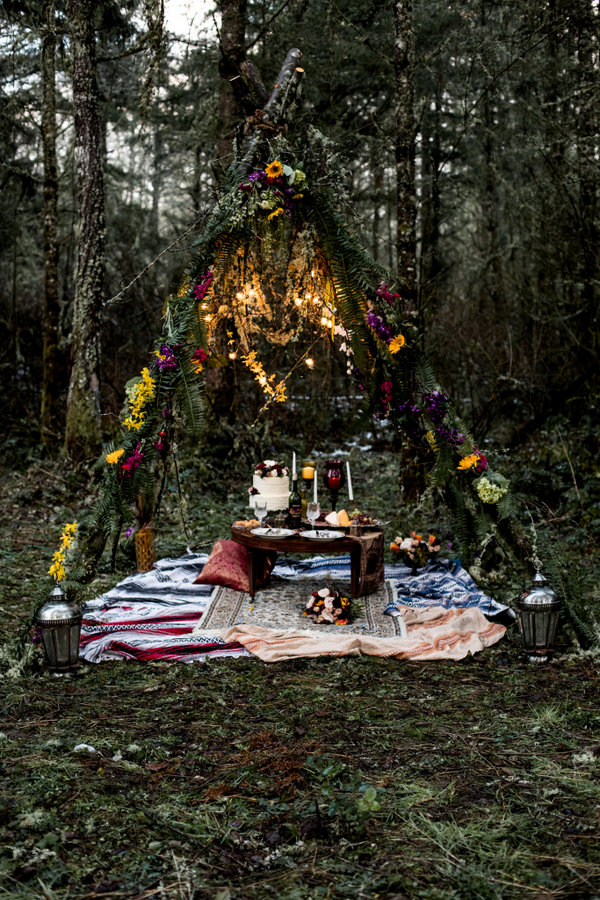 There was a teepee in the woods covered with ferns and colorful blooms and lights plus a picnic setting