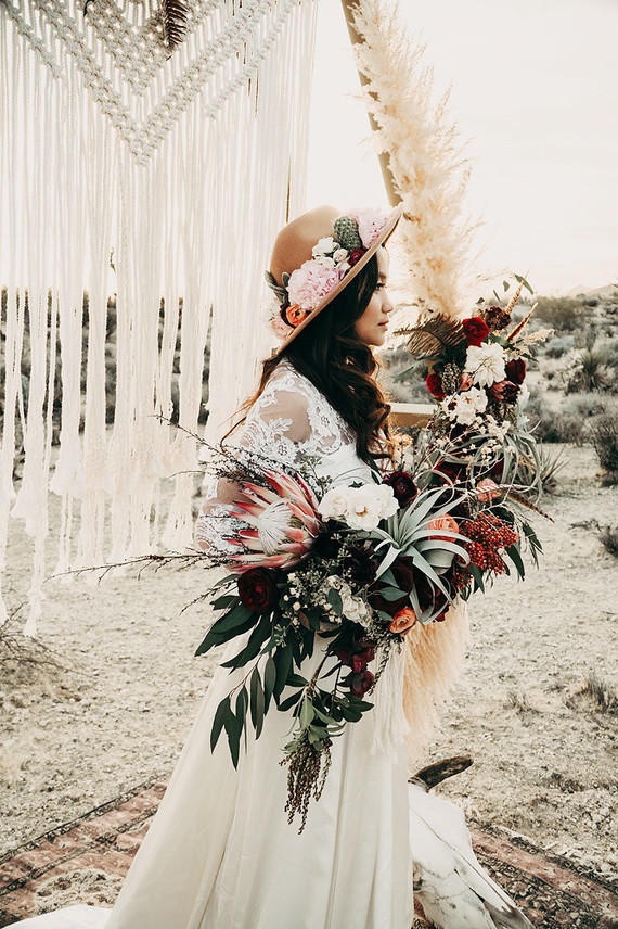 a boho bride with a lush bouquet and a hat decorated with blooms and cacti