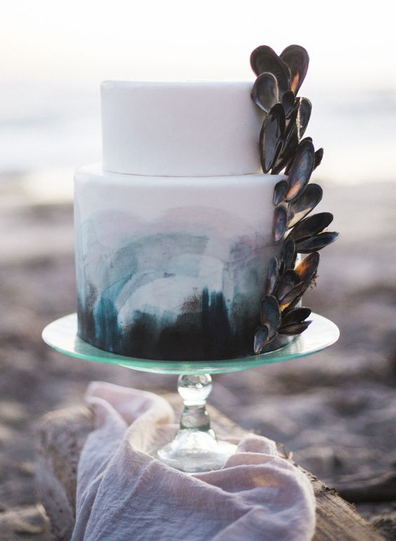 a bold seaside wedding cake with bold watercolor from turquoise to black and oyster shells on the side